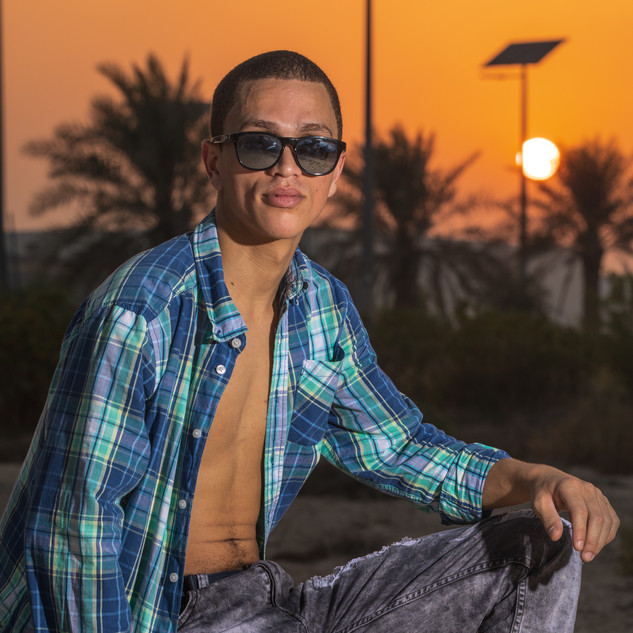 Male Model Sitting On A Rock During Sunset In The Desert