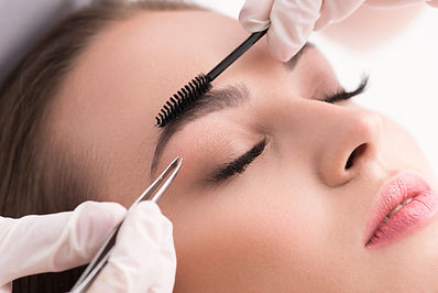 An eyebrow being shaped by plucking, waxing and threading