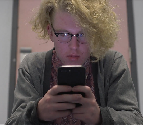 Blonde guy texting.png