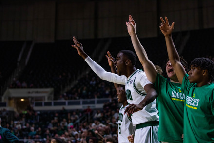 Ohio University basketball teammates cheer off the court during a game held at Ohio University's Convocation Center.