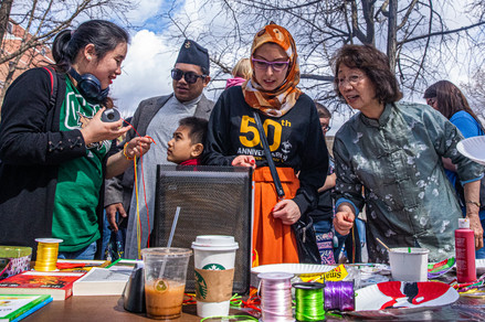 One of the many families attending the annual International Street Fair held in Athens, Ohio, talk amonst themselves at a craft booth on April 4, 2019.
