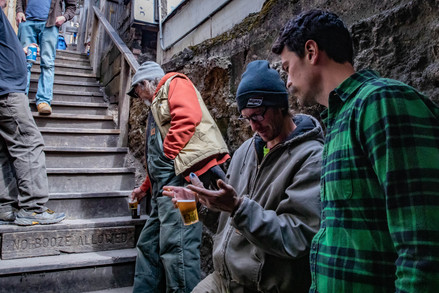 Nick Whitney (R) listens as Travis Fruge (L) explains how he injured his middle finger outside the Smiling Skull Saloon on Sunday, March 24, 2019.