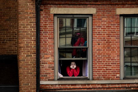 Marissa Owens watches the speakers at the Women's March from her window in uptown Athens on Jan. 19, 2019.