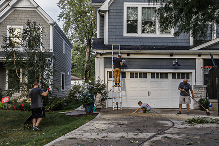 Neighbors support each other in cleaning up their yards and driveways in Elmhurst, IL, after a vicious derecho tore through Iowa to Chicago. Fallen branches, uprooted trees, destroyed roofs and hundreds of thousands without electricity  were left in the path of one of the most powerful storms that has ever hit the Chicago metropolitan area on Monday, Aug. 10, 2020.
