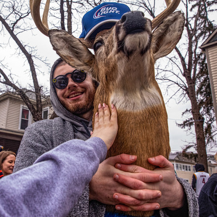 An Ohio University student carries a stuffed deer head around curious party-goers at the school's annual Mill Fest on March 2, 2019.
