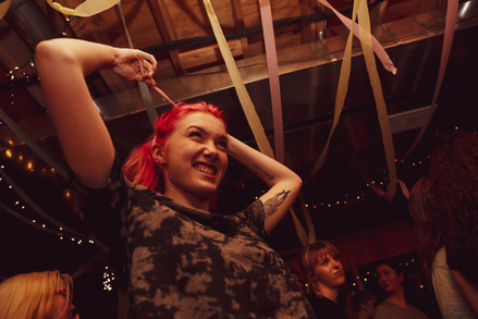 Gianna Wieczorek ties her hair back with a streamer at a basement house show concert with local high school alumni in Elmhurst, IL, on May 25, 2019.