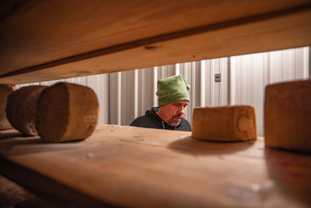 Chris Chmiel takes inventory of the cheeses he keeps in one of the many refrigerator units.