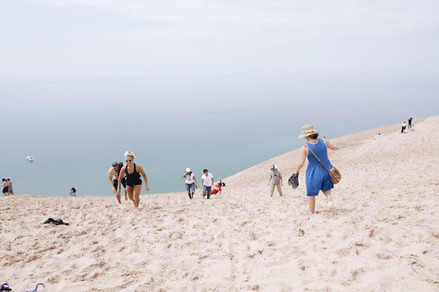 Tourists attempt to scale the steep slope of Sleeping Bear Dunes National Lakeshore on July 4, 2019.