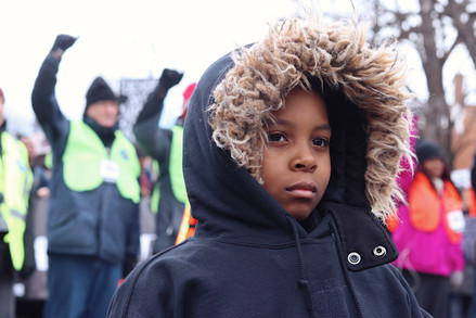 Organizers stand with their fists raised behind a young participant in the March for Our Lives demonstration held in Union Park, Chicago, on March 24, 2018.