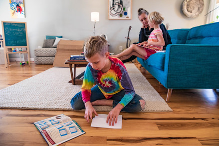 Abner constructs a paper plane while Coral helps her daughter, Eleanor, with math problems on the couch in their home in Albany, Ohio on a regular homeschool day on Monday, Nov. 4, 2019.