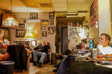 A group of men smoke cigars in Elmhurst Smoke Shop in Elmhurst, IL.