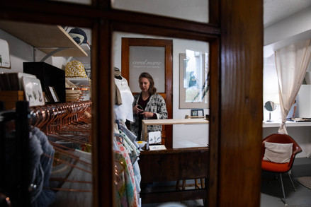 """Coral walks about her store inside her work studio, which is attached to her family home in Albany, Ohio. She started her own designer clothing company, """"Coral Marie"""" after marrying her husband, Matt."""