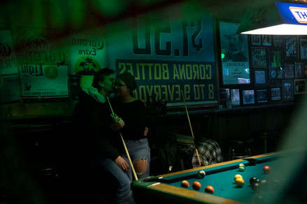 Sean Bailey gives a kiss to Savannah Medlen in the reflection of a sign during a game of pool at The Pub in Athens, Ohio.