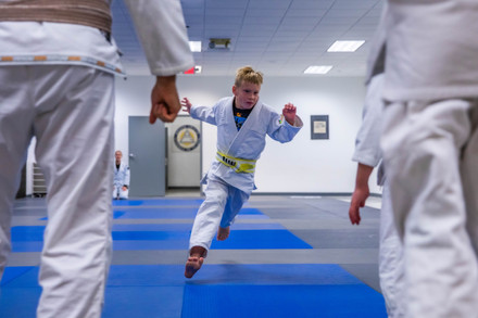 """Abner runs toward his teachers at Relson Gracie Jiu-Jitsu Academy in Athens, Ohio, on the morning of Friday, Nov. 8, 2019. Abner is working toward his yellow belt while his sister, Eleanor, works toward her """"banana belt"""" in a separate class at the same gym."""