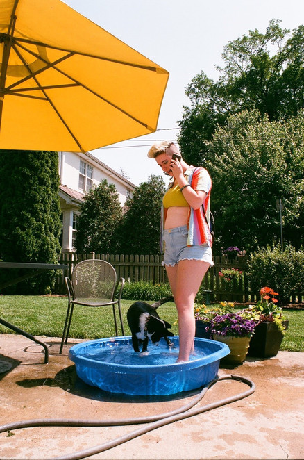 Ella Stanley talks on the phone while giving Milo a bath prior to leaving for the Chicago Pride Fest on June 19, 2018.