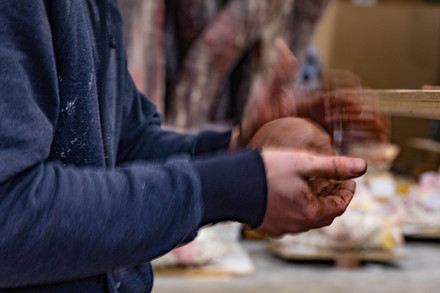 Matt Wedel tosses a ball of clay together to make clay ornaments with his childeren in his sculpture studio.