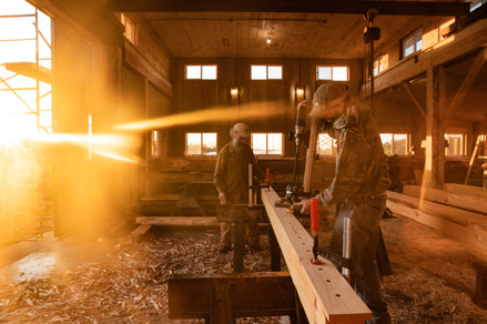 Chris Fox (center) receives help from Matt Hanson with wood framing in Fox's workshop while the morning sun rises for a day of transferring materials to his client's home on Sept. 18, 2019.