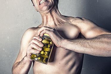 man struggles to open a pickle jar