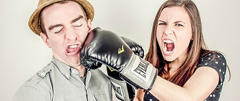a woman screaming and punching a man