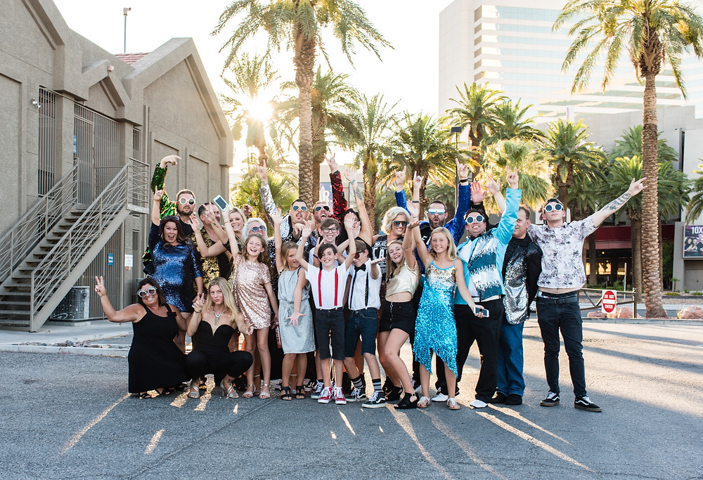 wedding party and guests pose for a fun photo outside a las vegas strip wedding chapel before the bride and groom vow renewal