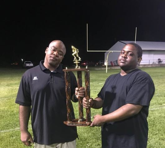Coach Brandon McKeever (right) celebrates the Arkansas Steelers' 2017 DCFL championship with Coach James Fuller.