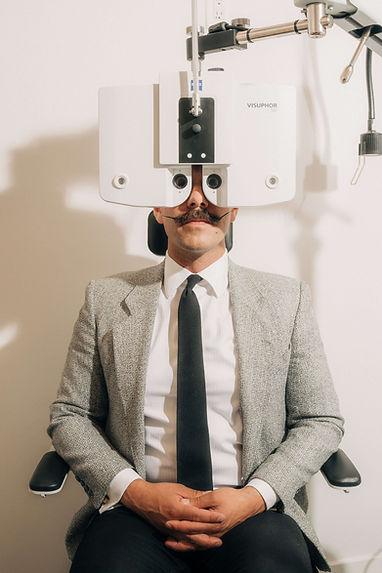 Eyeglasses shop with man in blazer sitting in exam chair looking through eye exam equipment.