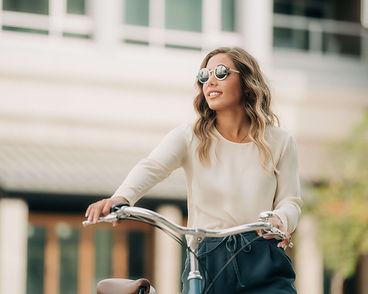 Beautiful eyeglasses Calgary: young women wearing round titanium eyeglasses walking her bicycle in Inglewood.
