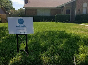 Residential Homw with front lawn and Adorable House sign.