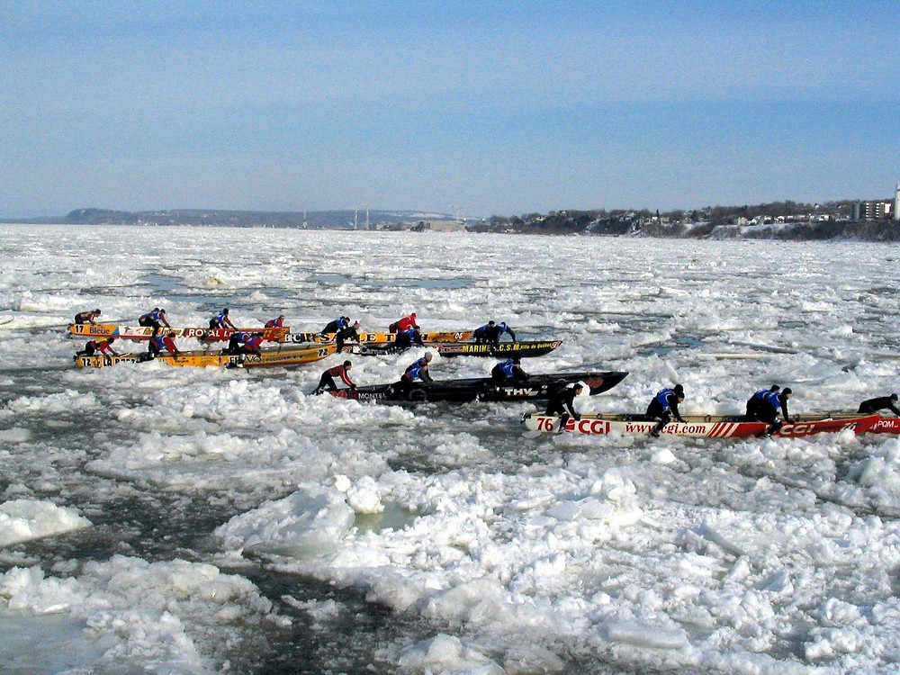 Alternately pushing the boat across ice and paddling the boat in strong current.