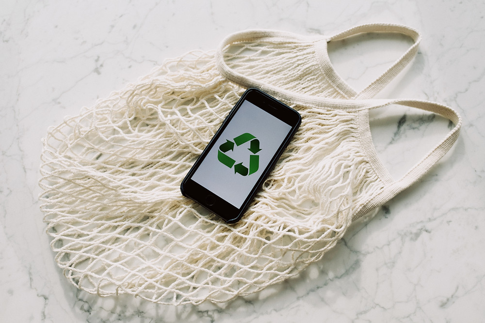 a phone showing a recycling symbol sits on a reusable bag