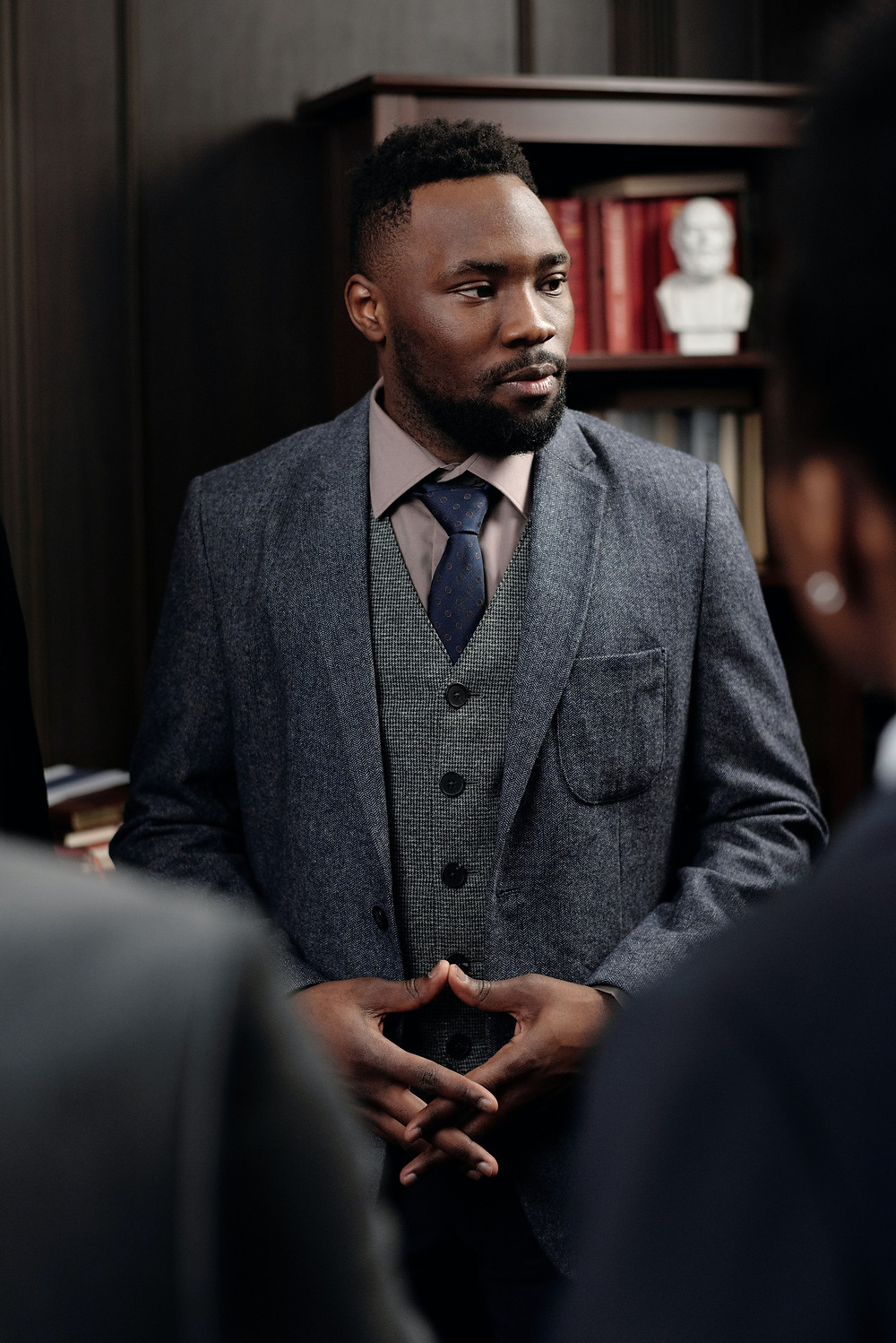A stylish man in a suit listening to his clients