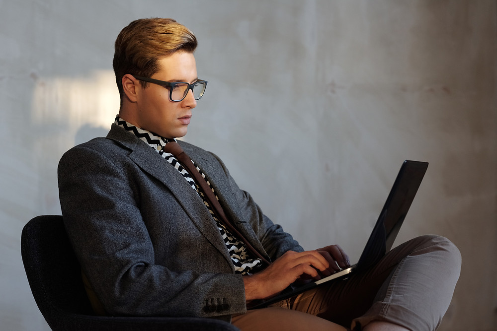 a man in a casual blazer and glasses works on his laptop