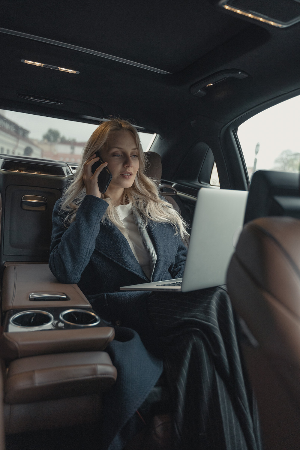 A woman takes a call while on her laptop in a car ride