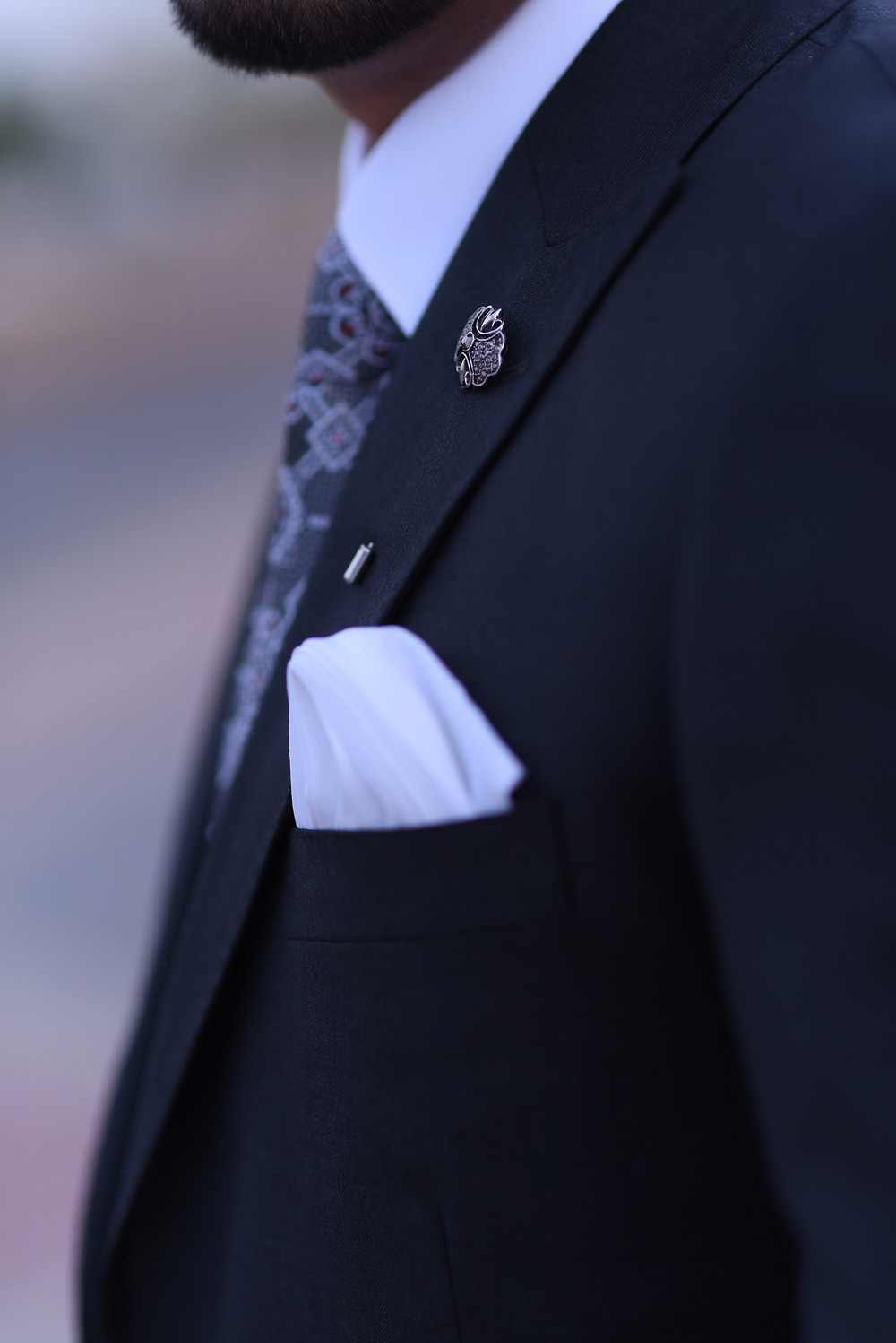 A man in a suit with a white pocket square