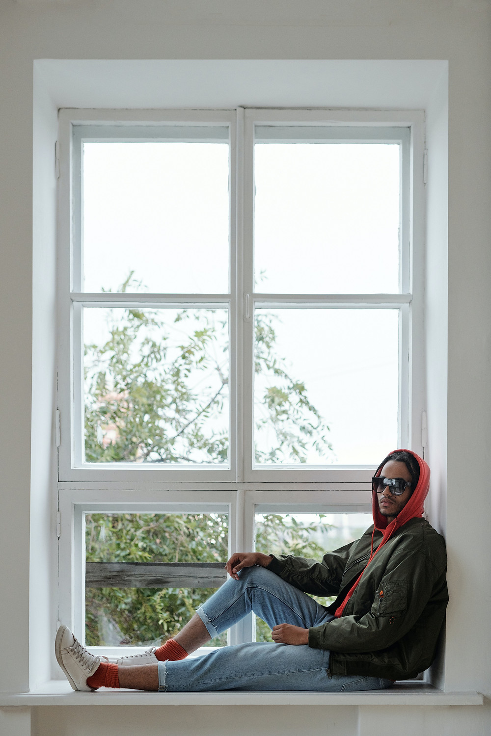 A man wearing a bomber jacket and jeans sits in a window