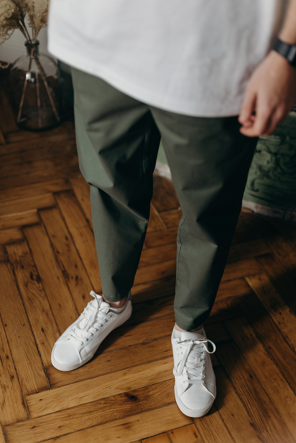 A man wearing a pair of white canvas sneakers