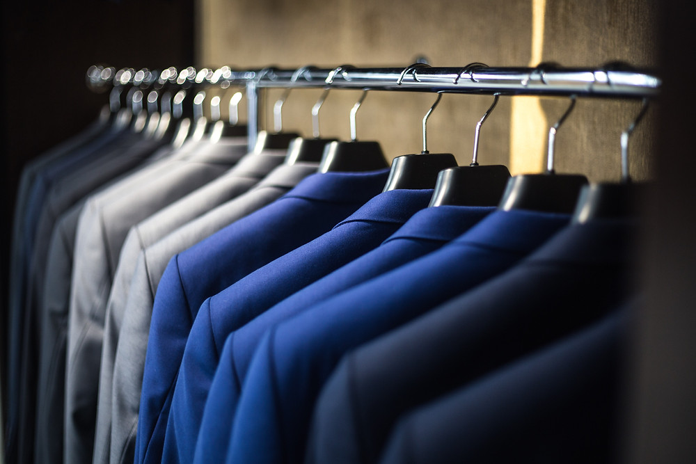 a rack of suit jackets in a range of different colours