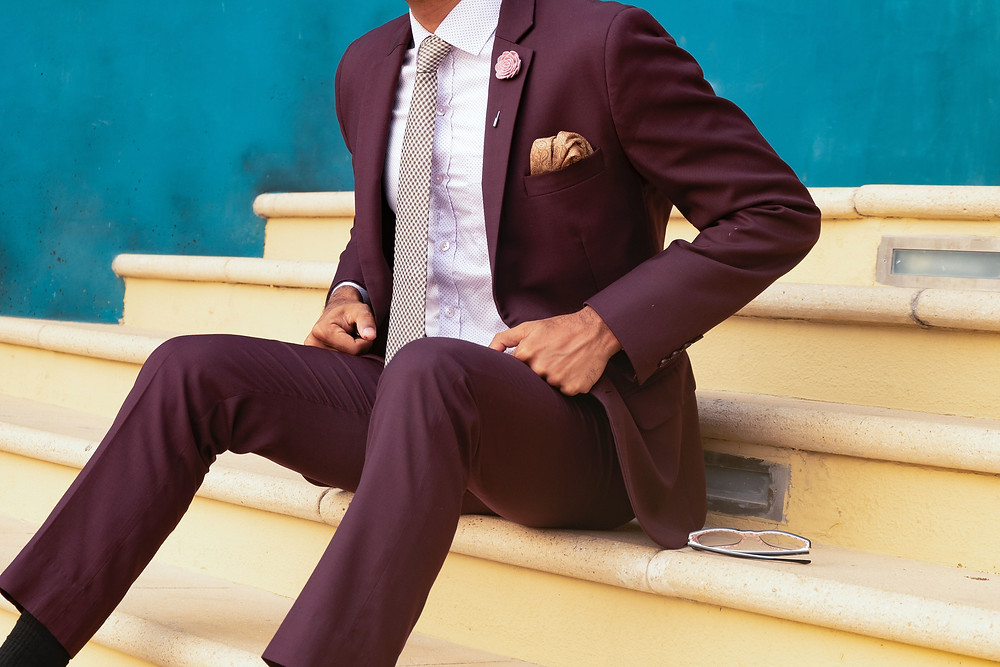 A man in a maroon suit with a golden pocket square