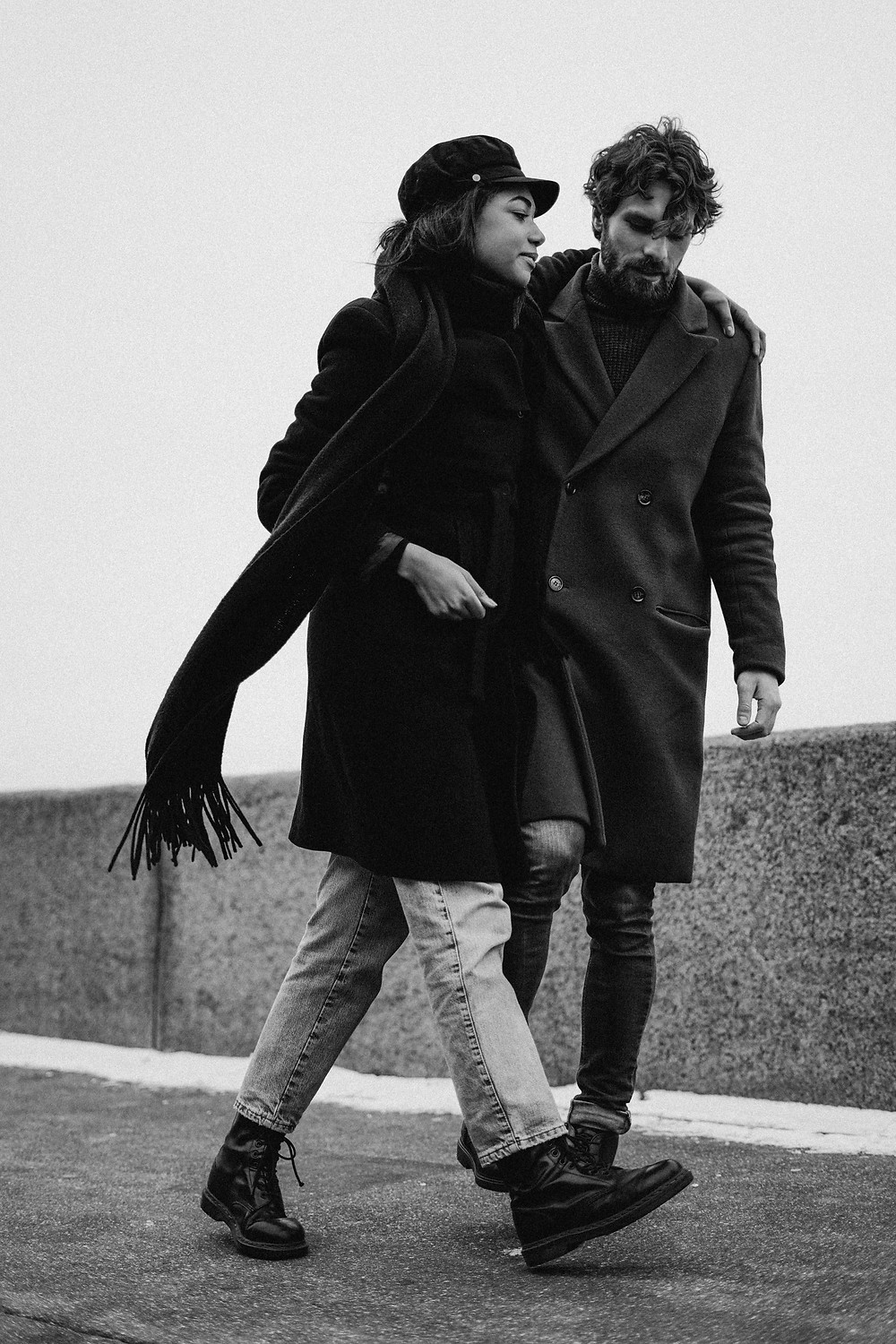 a man and a woman both in dark overcoats