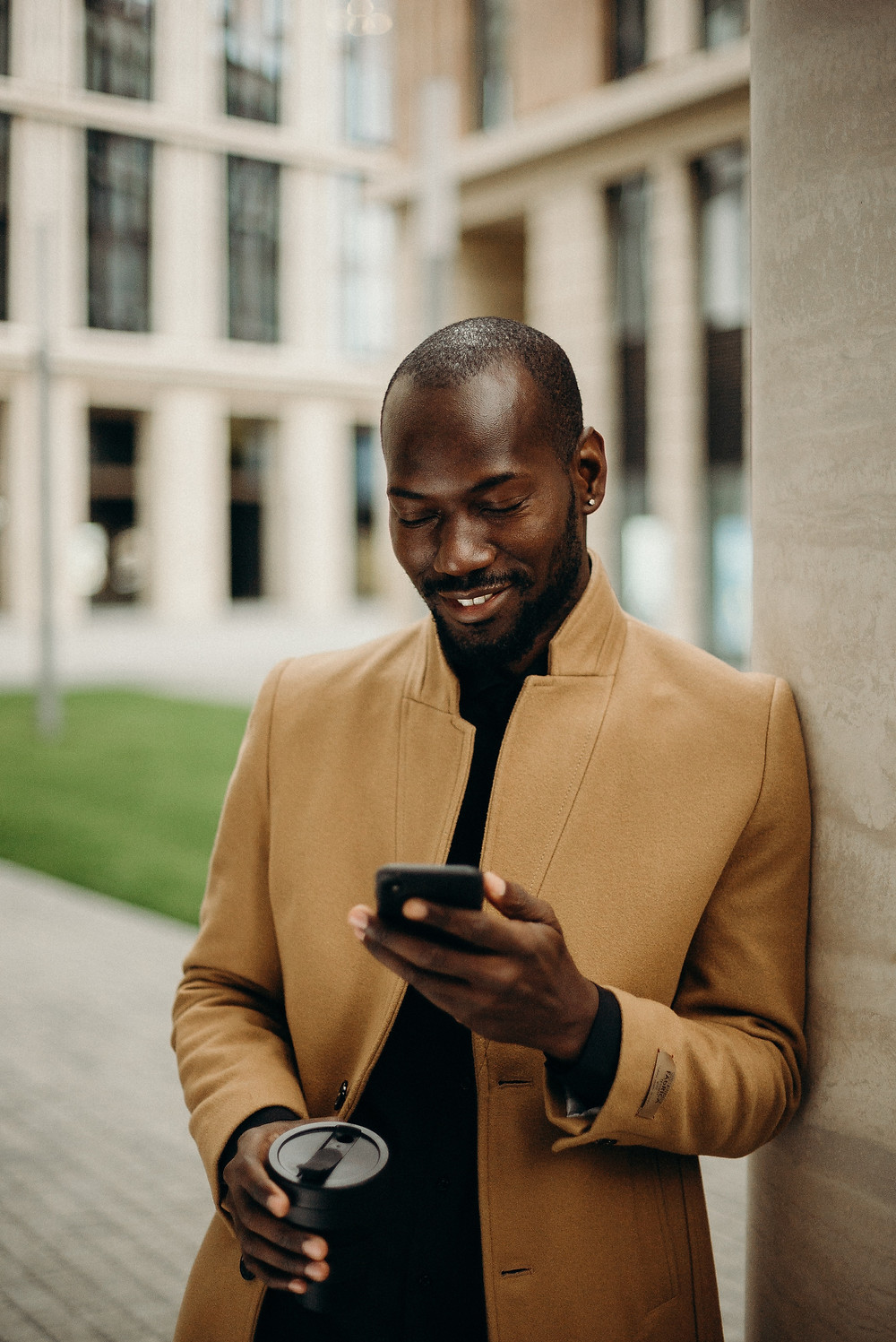 A well dressed man checks his phone