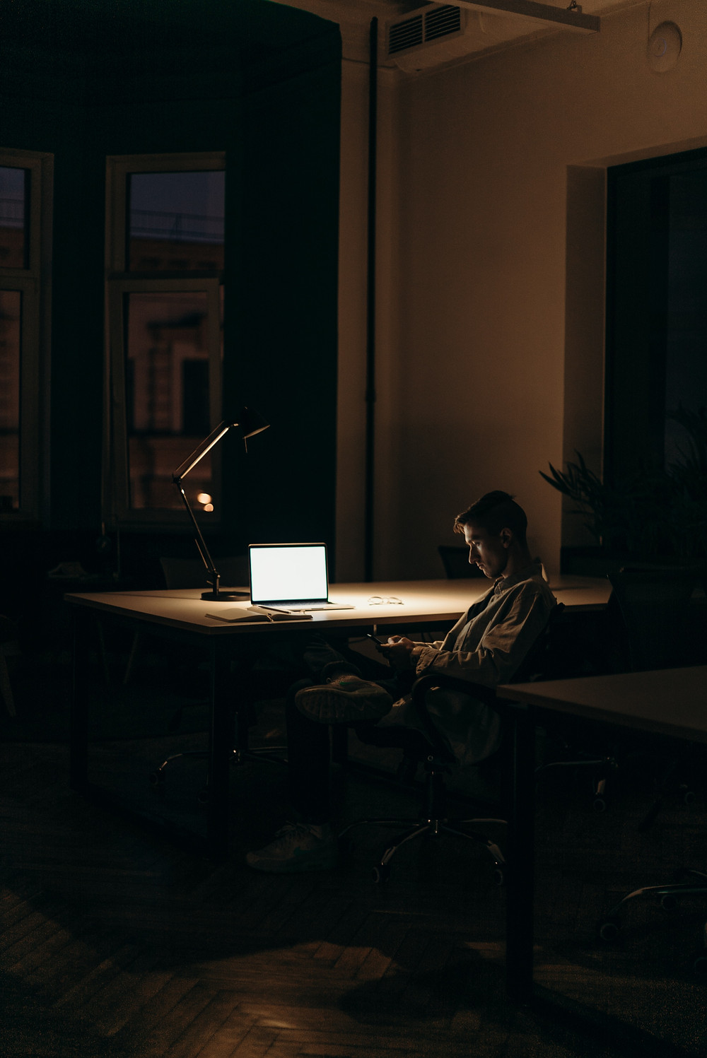 a man sits in a dark room infant of a bright laptop screen