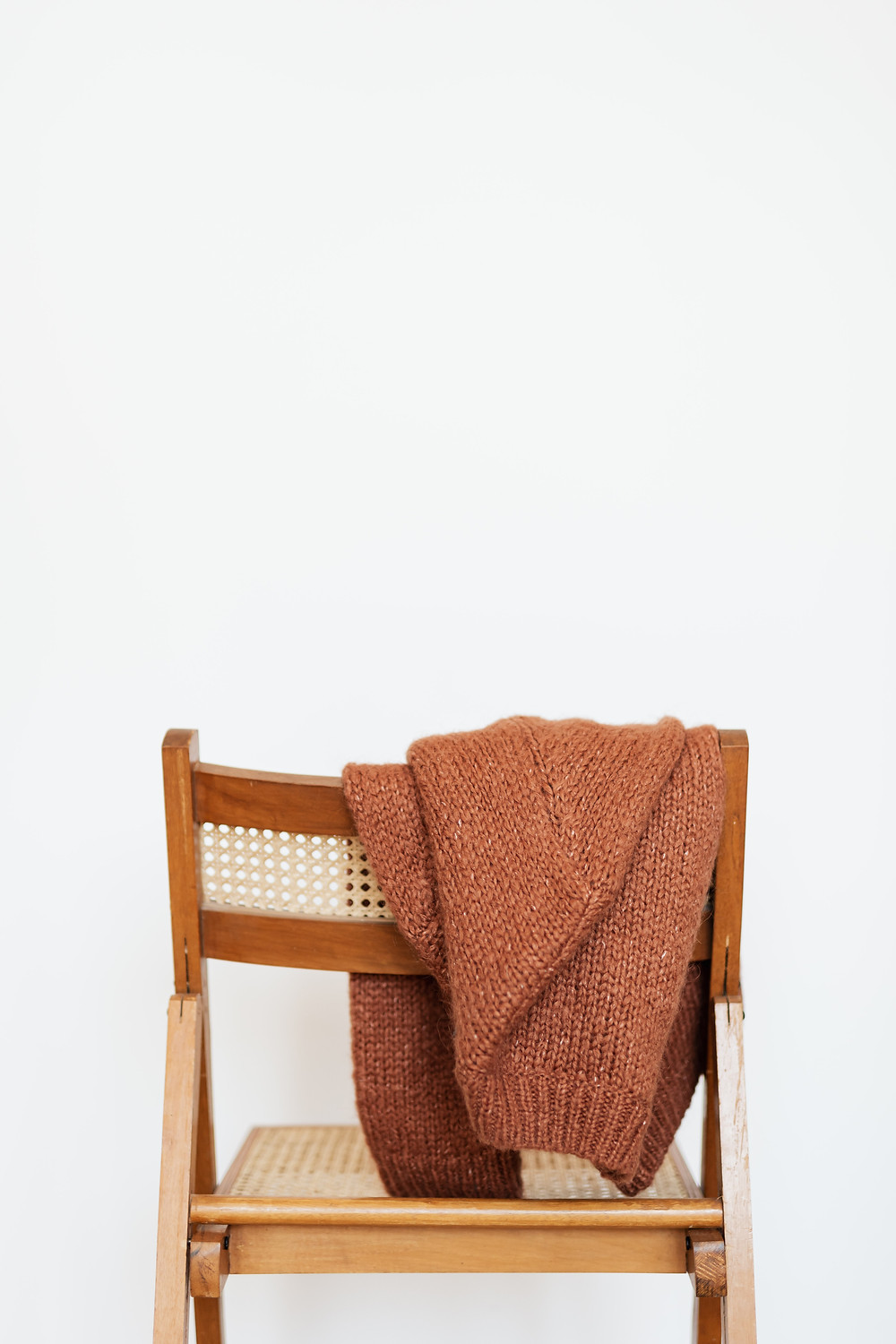 A natural toned knitted sweater hangs on a chair