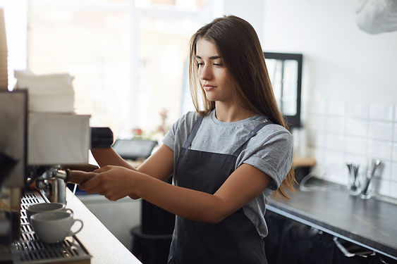 Young and sleepy female barista concentr