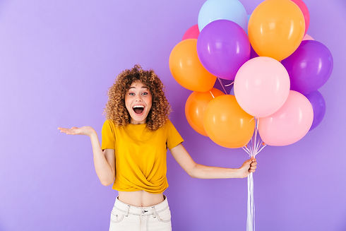 Image closeup of attractive delighted woman rejoicing while posing in multicolored air bal
