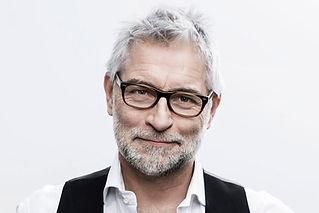 A-grey-haired-man-with-grey-beard-wearin