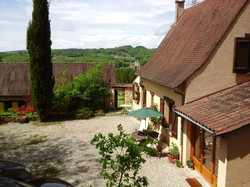 The house and courtyard from the garden with Chateau de Belcayre in background