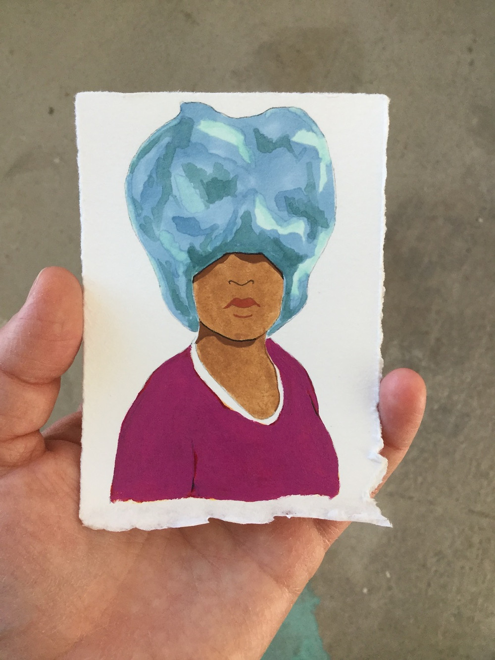 Raven Rohrig holding a small portrait.