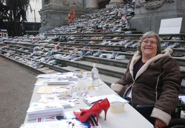 Pat Kelln, wearing a dark beige coat, in her wheelchair sitting at a desk. Pat has shoulder length grey hair, glasses, and is smiling.
