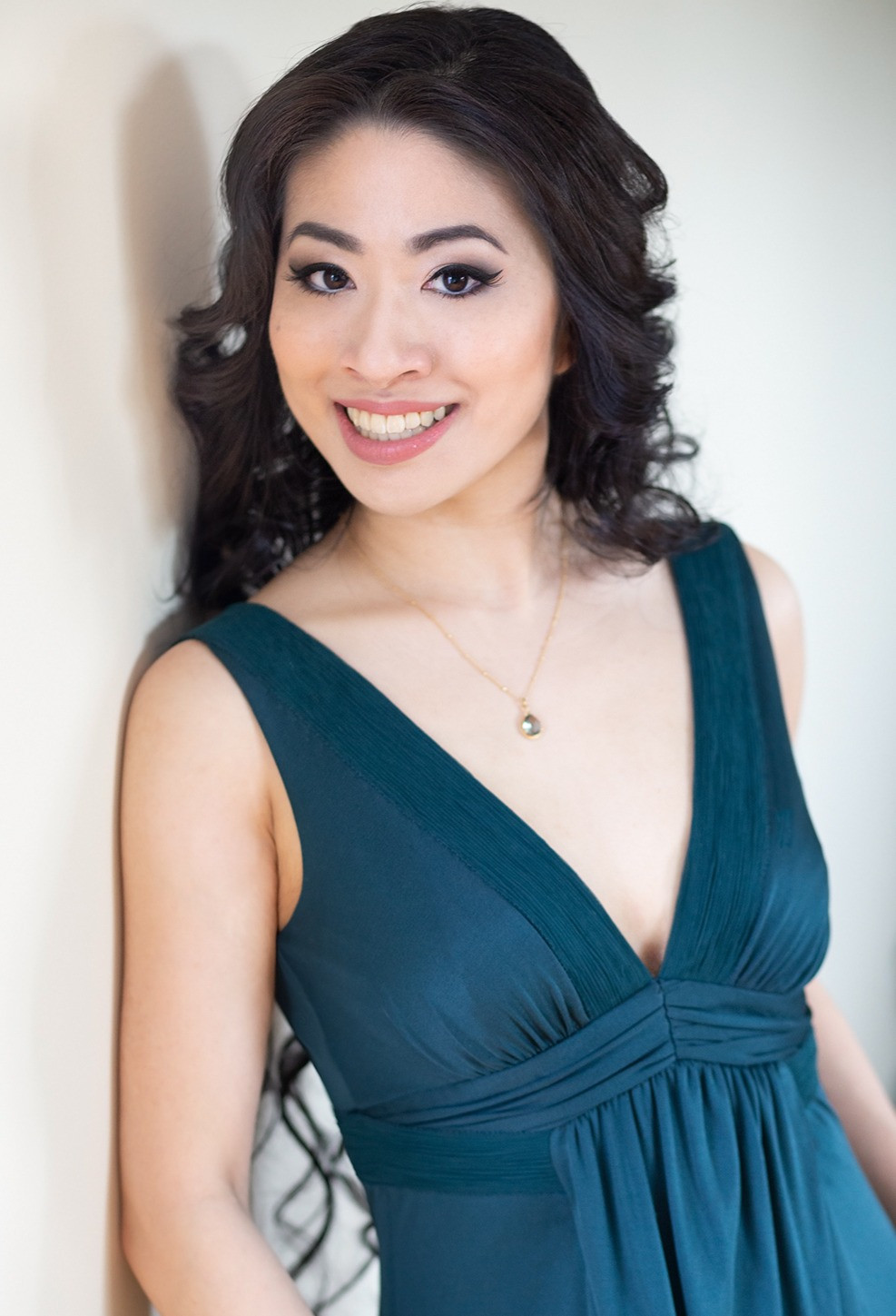 Stephanie Ko of Opera Mariposa smiles for the camera while wearing a green dress