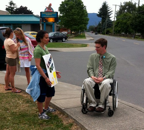 MLA Dan Coulter, who uses a wheelchair, talking with a member of the public.